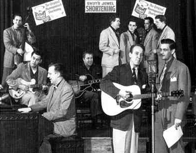 From left: Ernie Newton, Grady Martin, Owen Bradley, Jimmy Selph and The Jordanaires are among those accompanying Red Foley (at microphone) and WSM announcer David Cobb on an episode of the Swift's Jewel Shortening Show in 1950. (Image from www.billyrobinson.net)